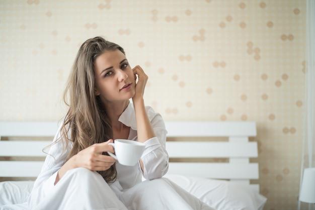Schönheit an ihrem trinkenden kaffee des schlafzimmers morgens Kostenlose Fotos