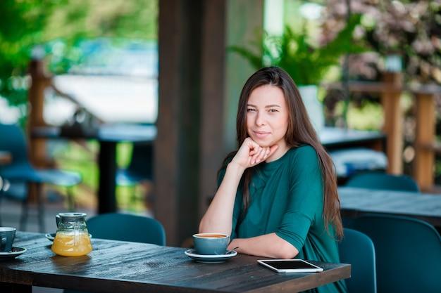 Schönheit, die café am im freien frühstückt. trinkender kaffee der glücklichen jungen städtischen frau Premium Fotos