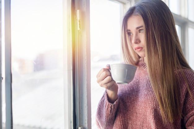 Schönheit, die durch das fenster hält eine tasse tee schaut Premium Fotos