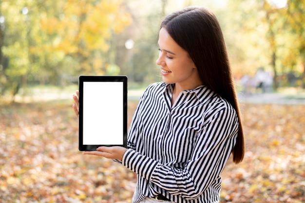 Schönheit, die eine tablette mit modell hält Kostenlose Fotos