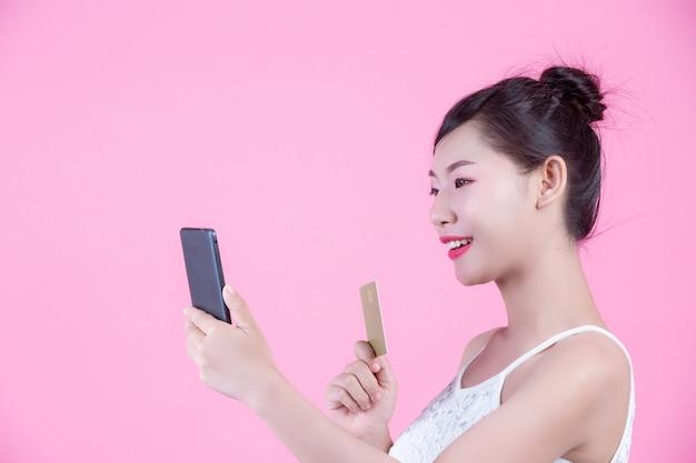 Schönheit, die einen smartphone und eine karte auf einem rosa hintergrund hält Kostenlose Fotos