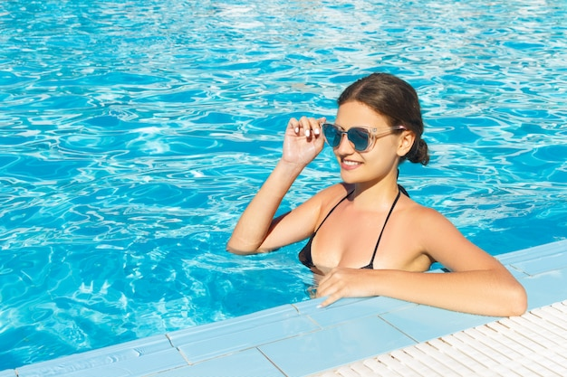 Schönheit, die in swimmingpool wasser in der sonnenbrille sich entspannt. Premium Fotos