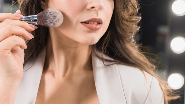Schönheit, die puder durch make-upbürste aufträgt Kostenlose Fotos