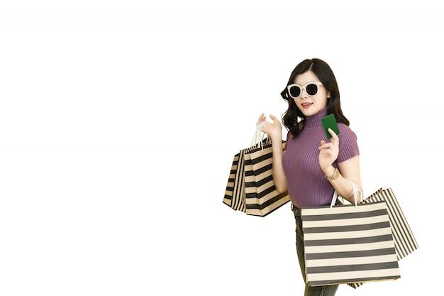 Schönheit kauft im mall unter verwendung der kreditkarte. tragende gläser der frau und halten einkaufstaschemode im kaufhaus. Premium Fotos