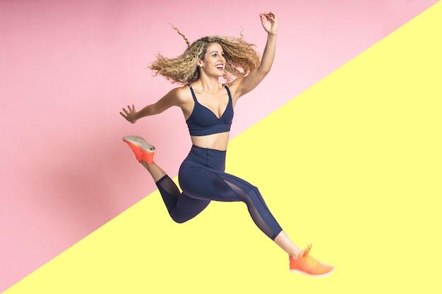Schönheit mit dem blonden gelockten haar mit nettem lächeln ist das glückliche lächeln und, das in der sportkleidung gekleidet wird, springt Premium Fotos