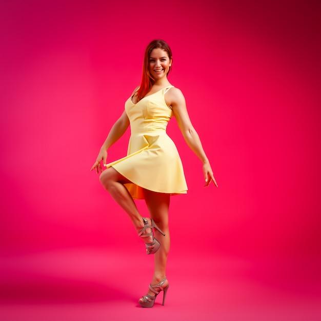 Schönheit mit dem gesunden körper, der in einem kleidertanzen trägt und herum auf rosa hintergrund spinnt. Premium Fotos