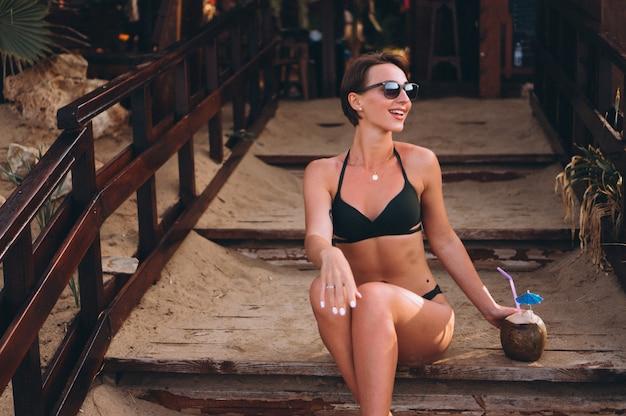 Schönheit mit der kokosnuss, die auf treppe in der stange sitzt Kostenlose Fotos