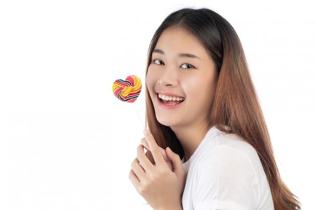 Schönheit mit einem glücklichen lächeln, das eine handsüßigkeit, lokalisiert auf weißem hintergrund hält. Kostenlose Fotos