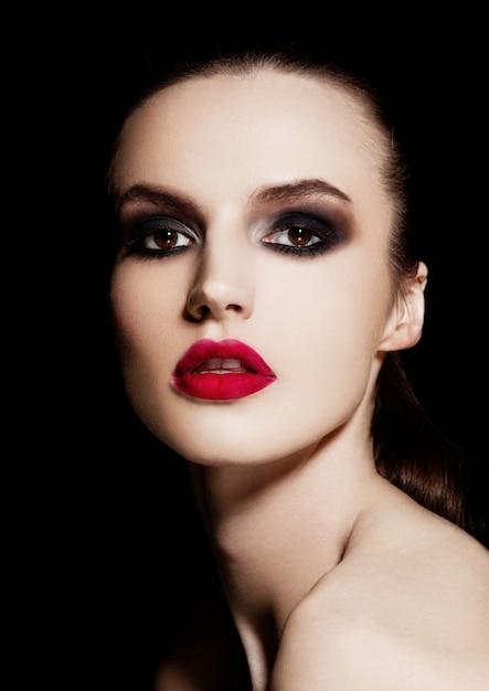 Schönheit smokey mustert rotes lippenmake-upmode-modell auf schwarzem hintergrund Premium Fotos