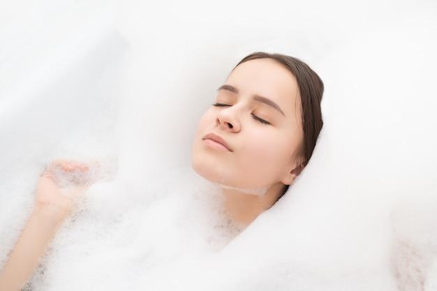 Schönheit, spa, körperpflege. junge frau entspannt sich im bad mit schaum Premium Fotos