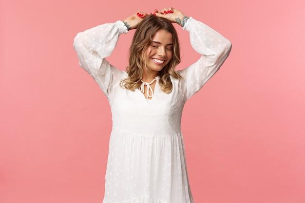 Schönheit, zärtlichkeit und modekonzept. attraktive blonde kaukasische frau mit tätowierungen im hellen weißen frühlingskleid, erhobene hände entspannt lächelnd mit geschlossenen augen, tanzend, rosa wand. Kostenlose Fotos