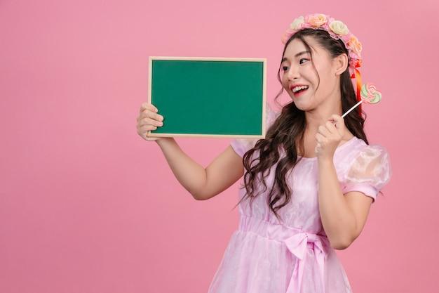 Schönheiten, die in den rosa prinzessinkleidern gekleidet werden, halten ein grünes brett auf einem rosa. Kostenlose Fotos