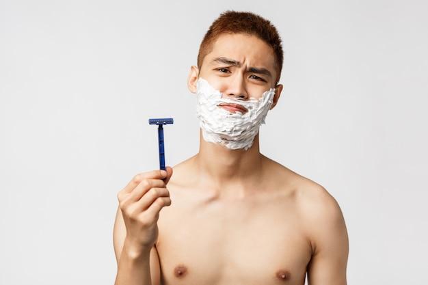 Schönheits-, menschen- und hygienekonzept. widerstrebender und missfallener asiatischer mann, der nicht bereit ist, sich zu rasieren, sieht enttäuscht aus, als würde die kamera das gesicht verziehen und altes rasiermesser zeigen, creme auf den kiefer auftragen, weiße wand Premium Fotos