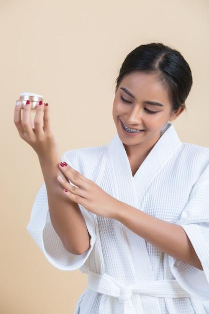 Schönheitsbehandlung mit frau hält eine feuchtigkeitscreme in der hand Kostenlose Fotos