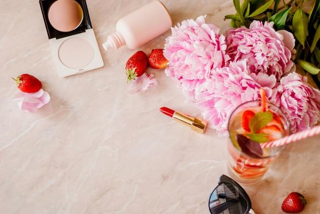 Schönheitsebene lag mit kosmetik, parfüm, detoxwasser mit erdbeere und pfingstrosen auf einem marmorhintergrund Premium Fotos