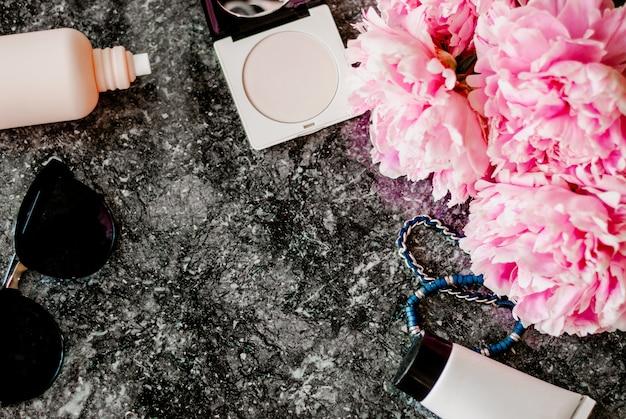Schönheitsebene lag mit zubehör, parfüm, kosmetik und pfingstrosen auf dunklem marmorhintergrund Premium Fotos