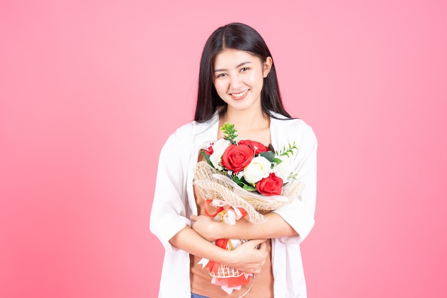 Schönheitsfrau asiatisches nettes mädchen fühlen sich glücklich, blumenrotrose und -weißrose auf rosa hintergrund halten Kostenlose Fotos