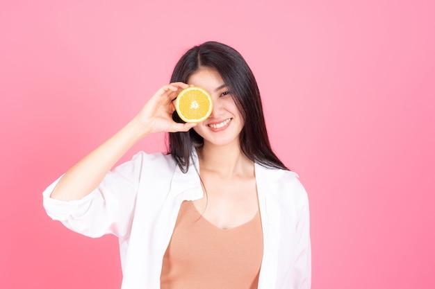 Schönheitsfrau asiatisches nettes mädchen fühlen sich glücklich holdind orange frucht für gute gesundheit auf rosa hintergrund Kostenlose Fotos