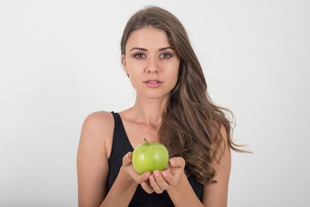 Schönheitsfrau, die grünen apfel hält, während sie auf weiß lokalisiert werden Kostenlose Fotos
