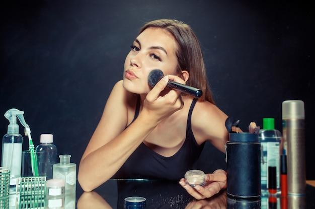 Schönheitsfrau, die make-up anwendet. schönes mädchen, das in den spiegel schaut und kosmetik mit einem großen pinsel anwendet. Kostenlose Fotos