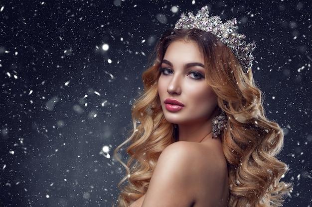 Schönheitsfrauengesicht mit schönen make-upfarben. das bild der königin. dunkles haar, eine krone auf dem kopf, klare haut, schönes gesicht, pralle lippen. Premium Fotos