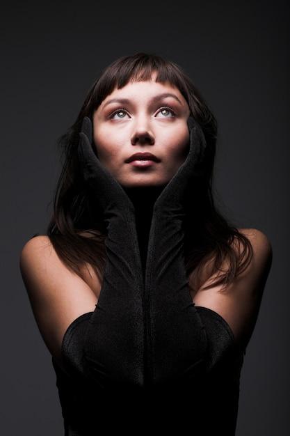 Schönheitsgebet in der dunklen, jungen frau Premium Fotos