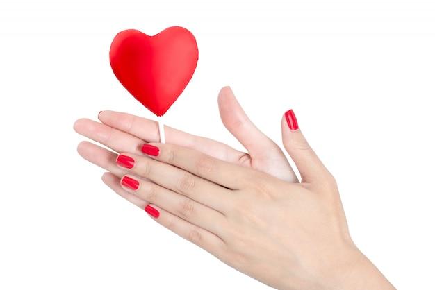 Schönheitshände mit dem roten nagel, der roten herzlutscher lokalisiert auf weißem hintergrund hält Premium Fotos