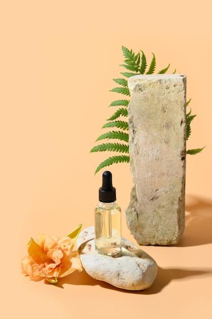 Schönheitskosmetiköl oder extraktion in glasflasche auf steinpodest verzierte frische blumen und pflanzenfarn auf beigem raum Premium Fotos