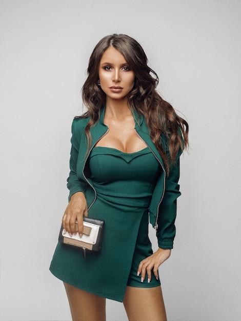 Schönheitsmädchen im modernen grünen overall und in den fersen. Premium Fotos
