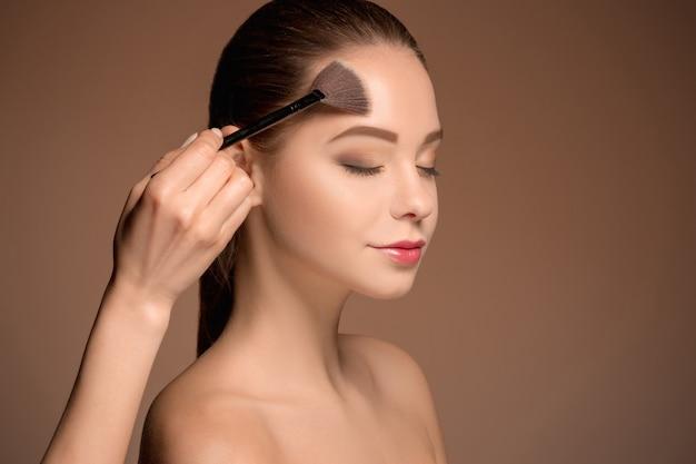 Schönheitsmädchen mit make-up pinsel. perfekte haut. make-up auftragen Kostenlose Fotos