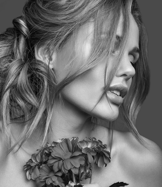 Schönheitsmodeporträt des jungen blonden frauenmodells mit natürlichem make-up und perfekter haut mit der hellen blumenaufstellung Kostenlose Fotos