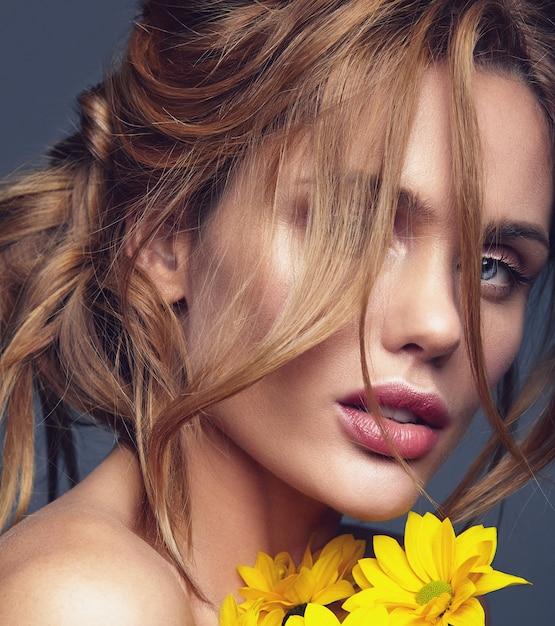 Schönheitsmodeporträt des jungen blonden frauenmodells mit natürlichem make-up und perfekter haut mit der hellen gelben chrysanthemenblumenaufstellung Kostenlose Fotos