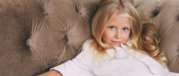 Schönheitsmodeporträt des lächelnden kleinen tweenmädchens mit dem angemessenen langen haar im weißen hemd auf beige sofahintergrundfahne, das modellieren der kinder Premium Fotos