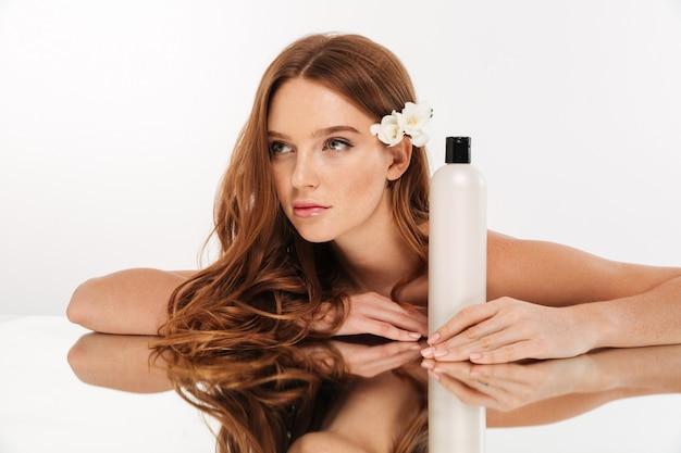 Schönheitsporträt der geheimnisingwerfrau mit blume im haar, das durch die spiegeltabelle mit flasche lotion beim weg schauen sitzt Kostenlose Fotos