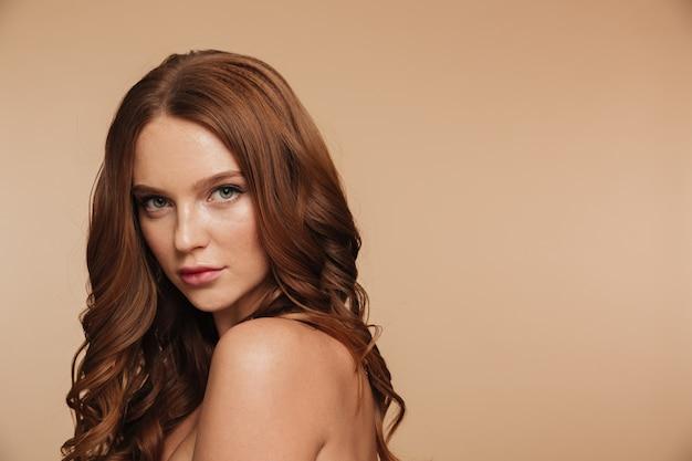 Schönheitsporträt der geheimnisingwerfrau mit dem langen haar, das seitlich aufwirft und schaut Kostenlose Fotos