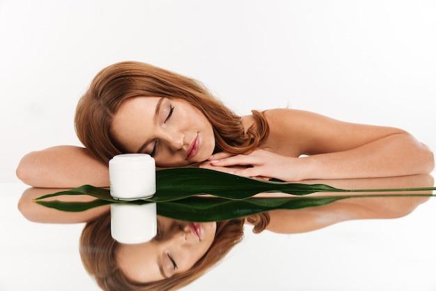 Schönheitsporträt der ingwerfrau mit dem langen haar, das auf spiegeltabelle mit creme für den körper und grünem blatt liegt Kostenlose Fotos