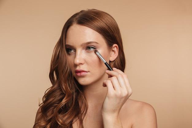 Schönheitsporträt der lächelnden ingwerfrau des geheimnisses mit dem langen haar, das beim auftragen von kosmetik mit bürste nach lidschatten weg schaut Kostenlose Fotos