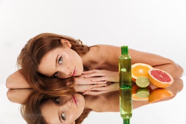 Schönheitsporträt der lächelnden ingwerfrau mit dem langen haar, das auf spiegeltabelle mit früchten und flasche lotin beim schauen liegt Kostenlose Fotos