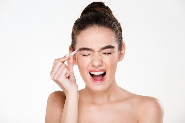 Schönheitsporträt der sinnlichen brunettefrau mit dem haar im brötchen schreiend in den schmerz beim zupfen von augenbrauen mit pinzette Kostenlose Fotos