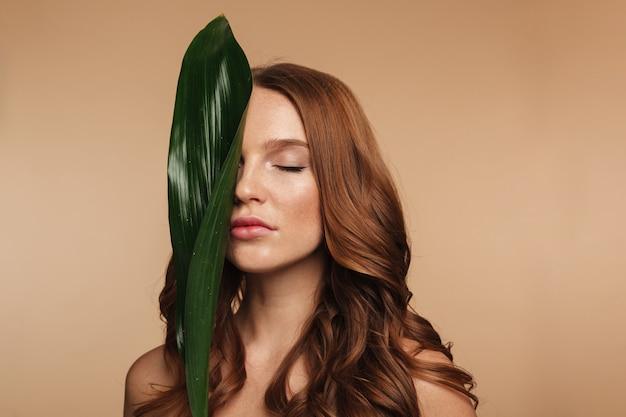 Schönheitsporträt der sinnlichen ingwerfrau mit dem langen haar, das mit grünem blatt aufwirft Kostenlose Fotos