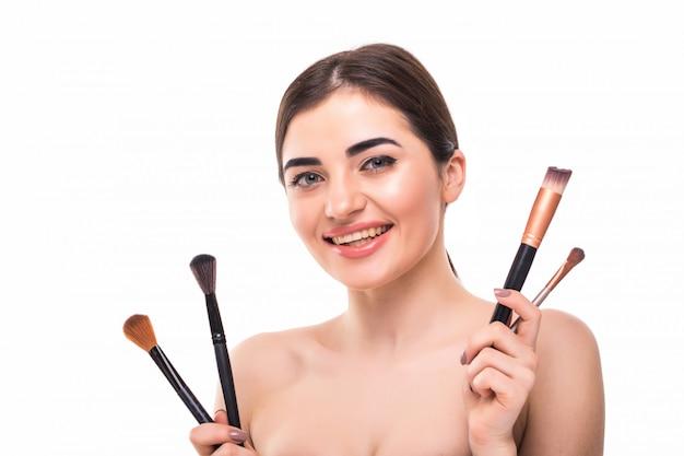 Schönheitsporträt einer glücklichen schönen halbnackten frau, die satz make-up pinsel hält Kostenlose Fotos