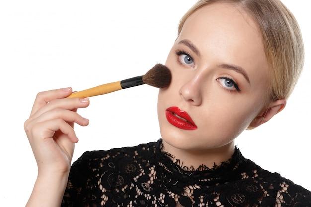 Schönheitsporträt einer lächelnden schönen halben nackte, die mit make-upbürsten aufwirft Premium Fotos