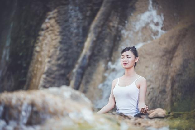 Schönheitssitzen und übendes yoga. Premium Fotos