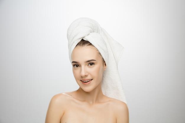 Schönheitstag. frau, die handtuch lokalisiert auf weißem studiohintergrund trägt. tag für selbstpflege, hautpflege, schönheitsroutine. Kostenlose Fotos