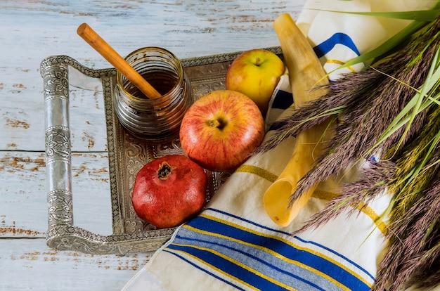 Schofar, honig, apfel und granatapfel über holztisch. Premium Fotos