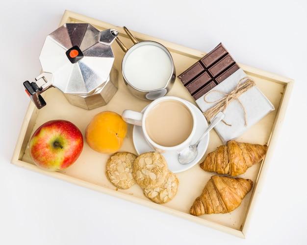 Schokolade, croissant, apfel, kekse, milch und tee zum frühstück Kostenlose Fotos