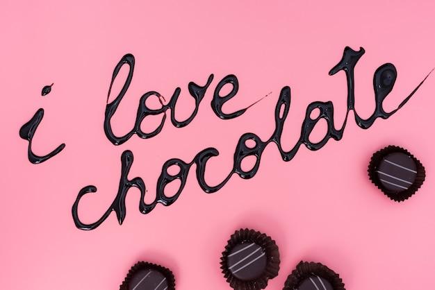 Schokoladen auf rosa hintergrund mit schokoladensirupschreiben Kostenlose Fotos