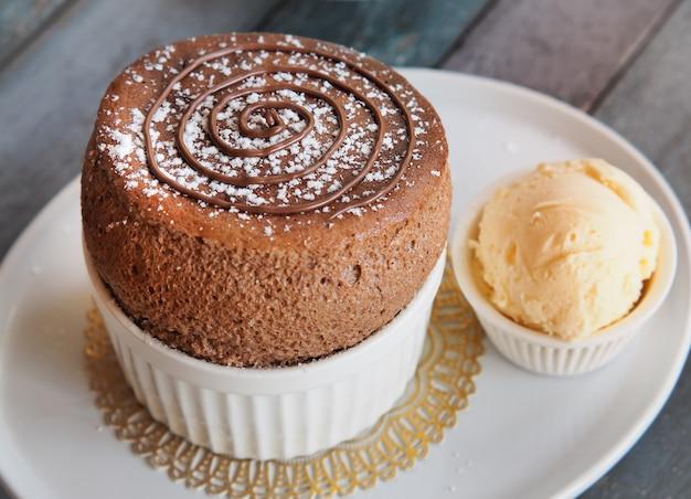 Schokoladen-auflauf mit vanilleeis auf weißer platte. französischer traditioneller nachtisch. Premium Fotos