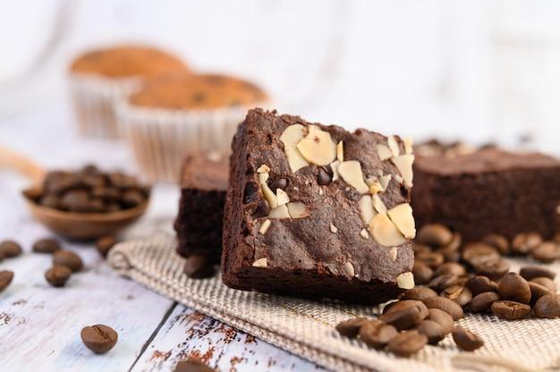 Schokoladen-brownies auf sackleinen und kaffeebohnen auf einem holztisch. Kostenlose Fotos