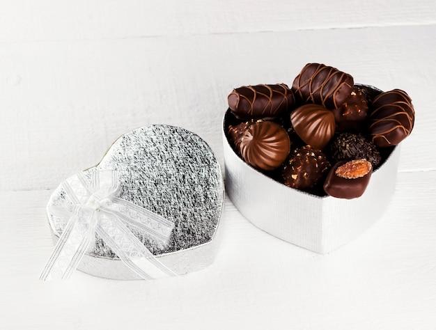 Schokoladen in einem kasten in der form des herzens auf einem weißen hintergrund Premium Fotos